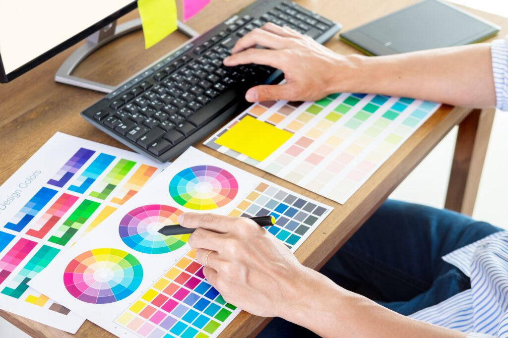 Graphic designer or creative holding Mouse and do his work material color pantone swatch samples art